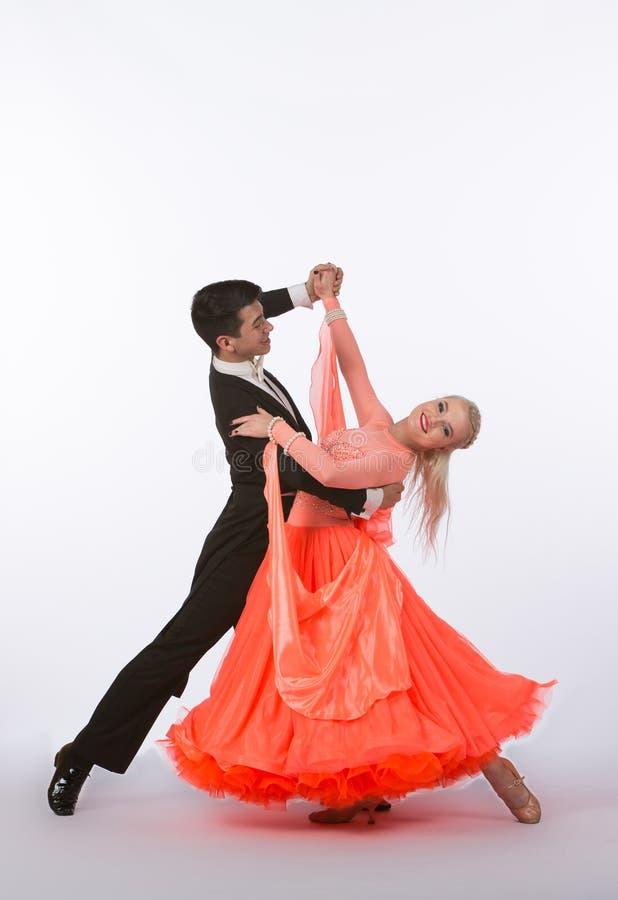 Balsaldansare med den orange klänningen arkivfoto
