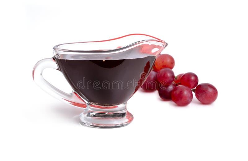Balsamic vinäger i bunke med druvan bakgrund isolerad white royaltyfria bilder