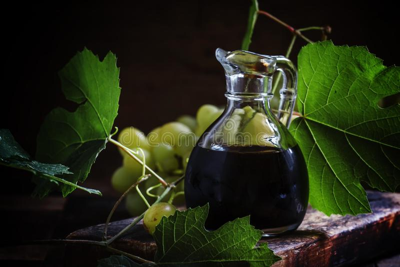 Balsamic vinegar in a glass jug, vintage wooden background, rust stock images