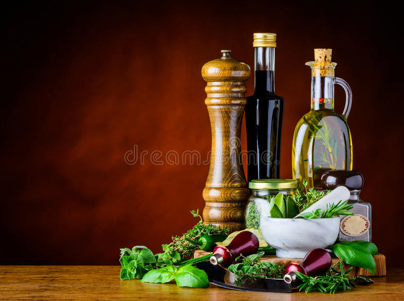 Balsamic Vinegar, Olive Oil and Green Herbs. Salt mill, balsamic Vinegar and olive oil with green herbs in still life with copy space royalty free stock photos