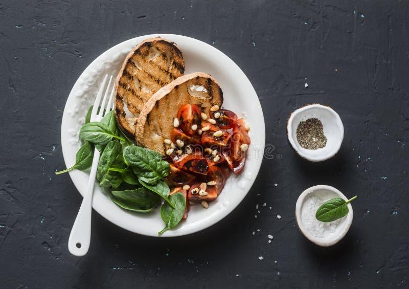 Balsamischer marinierter Kirschtomatensalat mit Kiefernnüssen, Spinat und gegrilltem Brot auf dunklem Hintergrund, Draufsicht lizenzfreie stockfotos