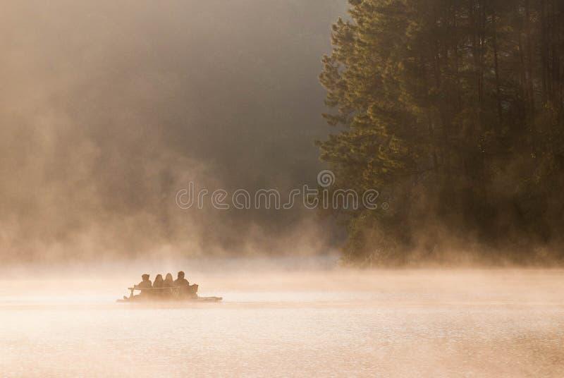 Balsas de bambú que flotan en el agua brumosa con luz del sol foto de archivo libre de regalías