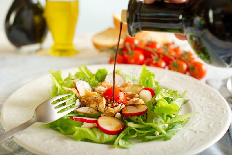 Balsemieke azijn op kippensalade stock afbeelding