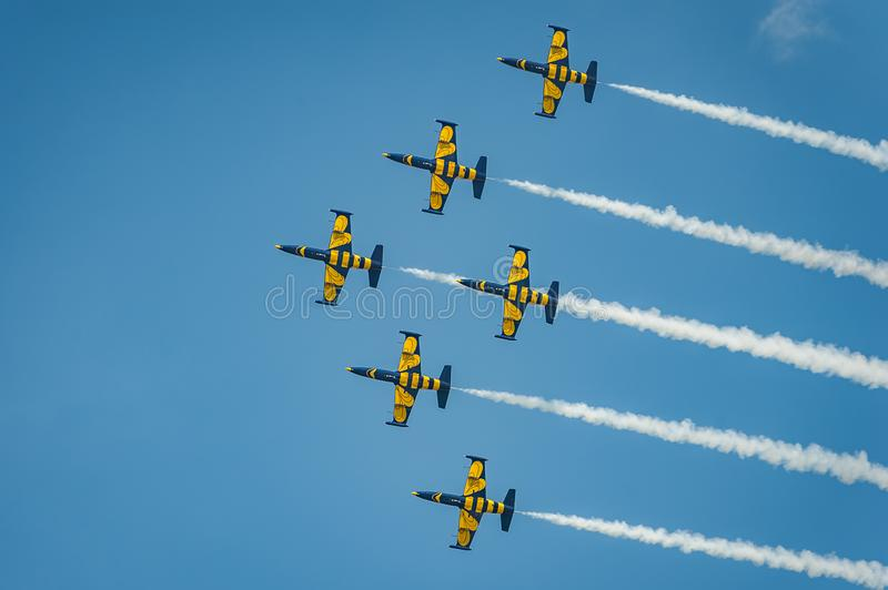 Baltic Bees team performs flight at air show and leaves behind a smokes in the sky royalty free stock images