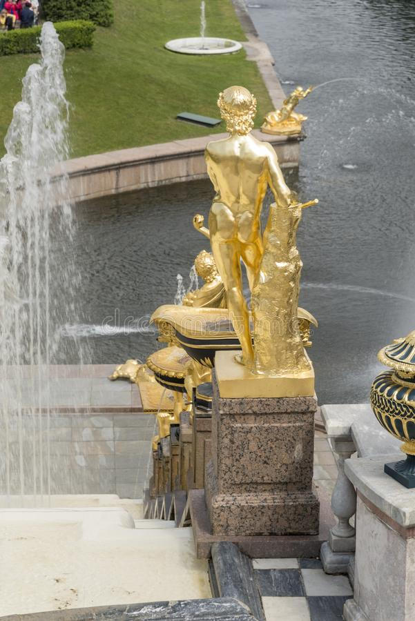 Golden Statue of the Grand Cascade in Peterhof Palace St Petersburg Russia. Majestic ensemble of fountains with unique, opulent architecture & golden statues royalty free stock image