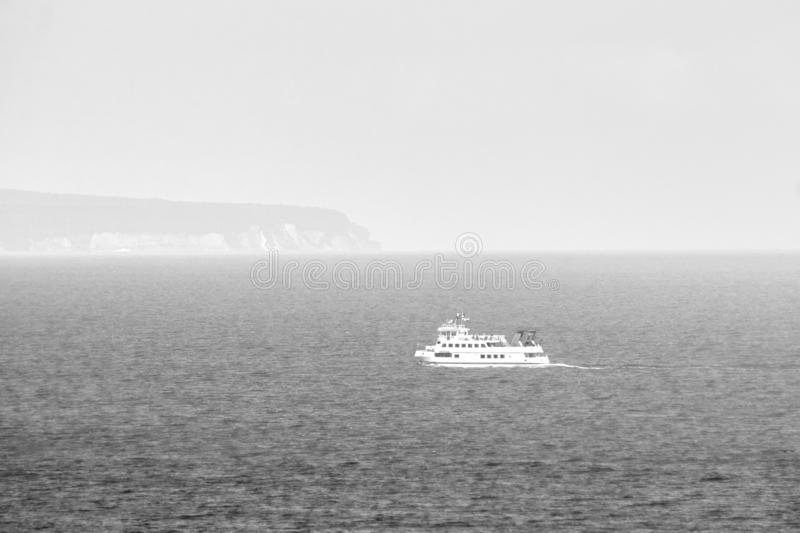 Baltic Sea ferry sails into the fog. Baltic Sea ferry enters the fog off the coast of the German island Ruegen, alarming atmosphere, blackwhite stock image