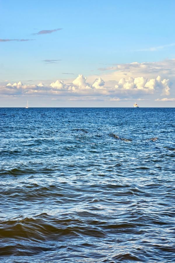 Baltic Sea with sailboat and industrial ship under beautiful clouds royalty free stock image