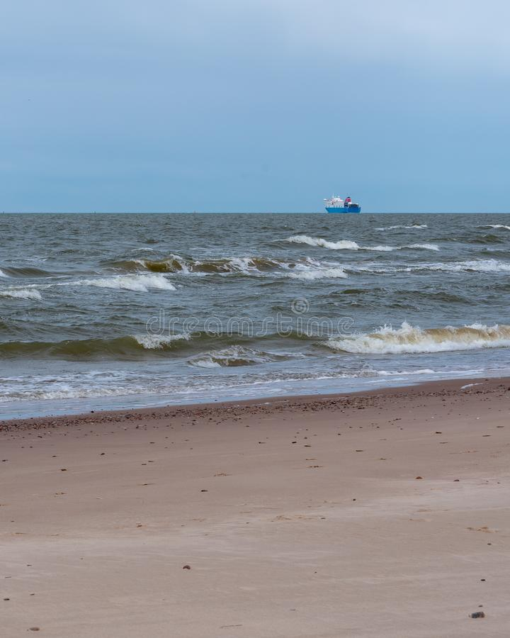 A large ship sailing away. The Baltic Sea sandy beach with small stones and a large ship sailing away; beautiful blue sky above the horizon royalty free stock image