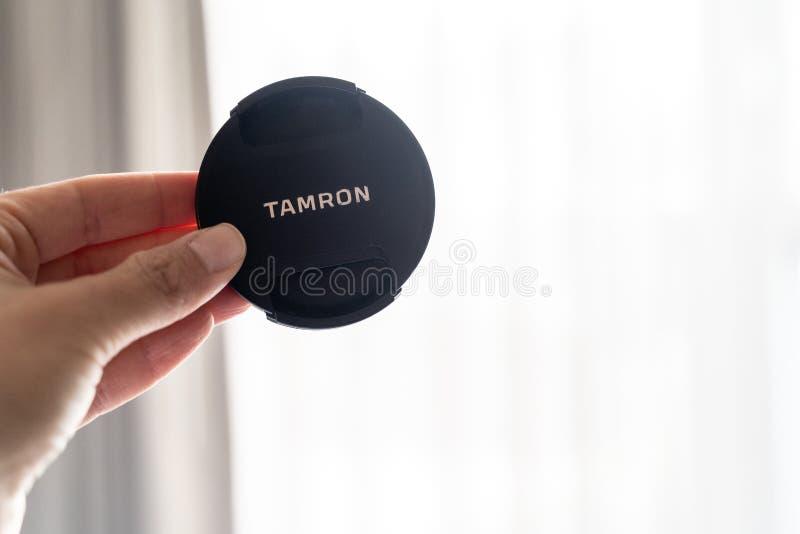 Baltimore, Maryland - 14 de mayo de 2019: La mano soporta un casquillo de lente de c?mara de la marca de Tamron para una c?mara d fotografía de archivo libre de regalías