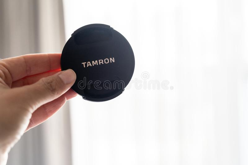 Baltimore, Maryland - May 14, 2019: Hand holds up a Tamron brand camera lens cap for a DSLR camera. This is a third party brand of. Lenses, for Sony, Canon and royalty free stock photography