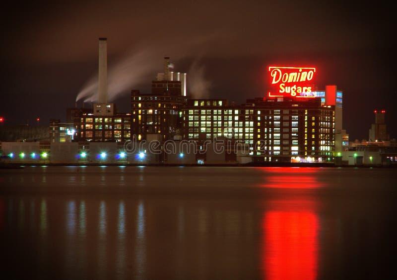 Baltimore MD— Oktober 12, 2017, historisk dominobrickasockerfabrik som reflekterar längs den Baltimore hamnen på natten royaltyfria foton