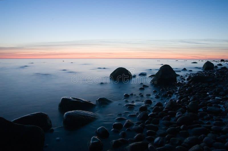 Baltische Küste mit Steinen nach Sonnenuntergang lizenzfreie stockfotografie