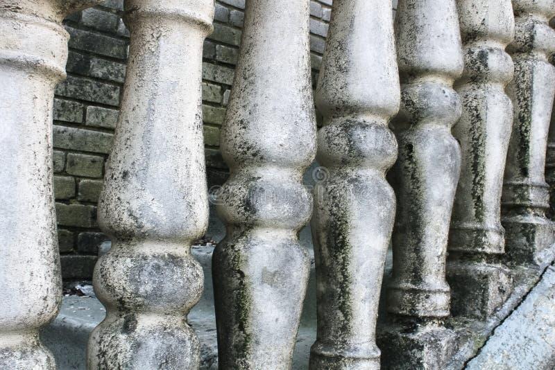 Baluster gjorde av stenen p? den gamla historiska trappuppg?ngen Fördärvar av tappningbaluster Grå färger red ut stenbaluster _ royaltyfria foton