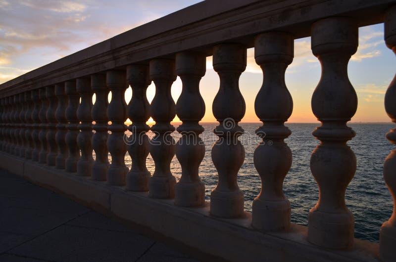 Balustrade mit Sonnenuntergang im Meer hinten stockbilder