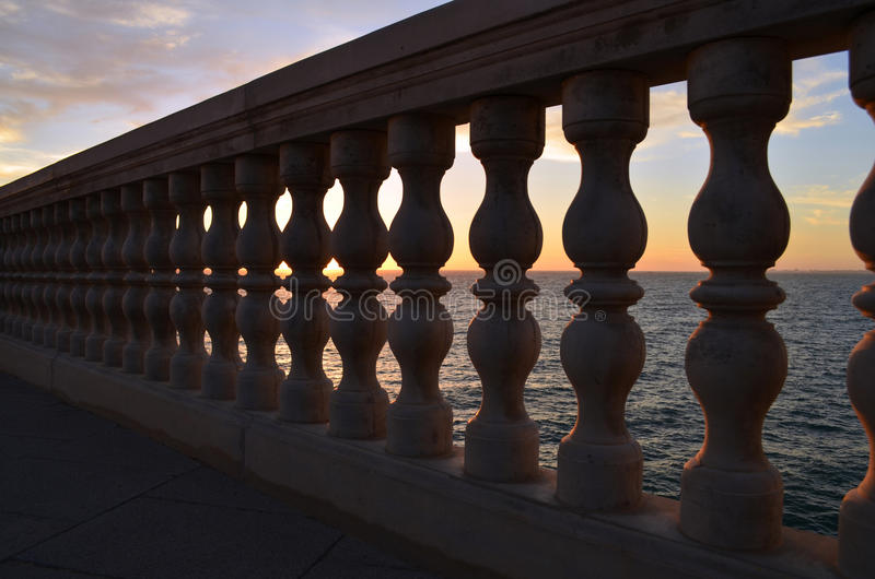 Balustrade with sunset in the sea behind stock images