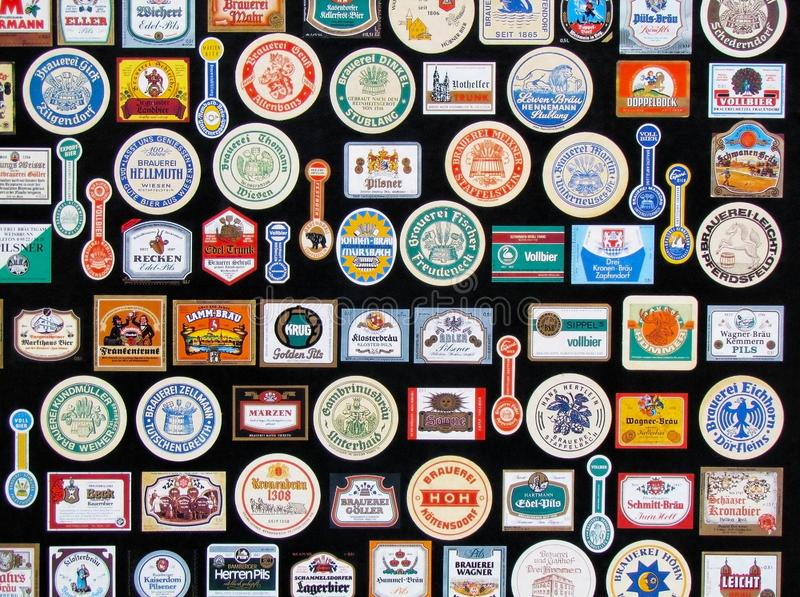 Fragment of collection of vintage beer labels set out as decoration in a pub. Beer bottle stickers and coasters isolated on black royalty free stock images