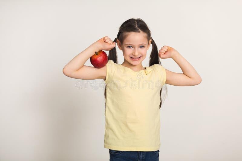 Bambina abbastanza sveglia con la mela rossa sopra fondo bianco fotografia stock libera da diritti