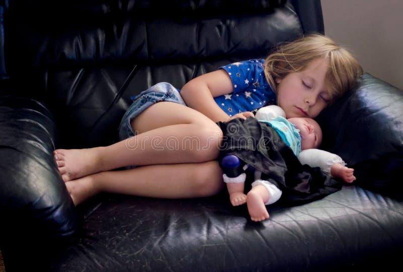 Bambina addormentata con la bambola immagini stock libere da diritti