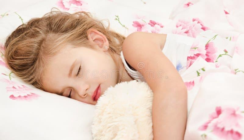 Bambina adorabile che dorme nel letto fotografia stock