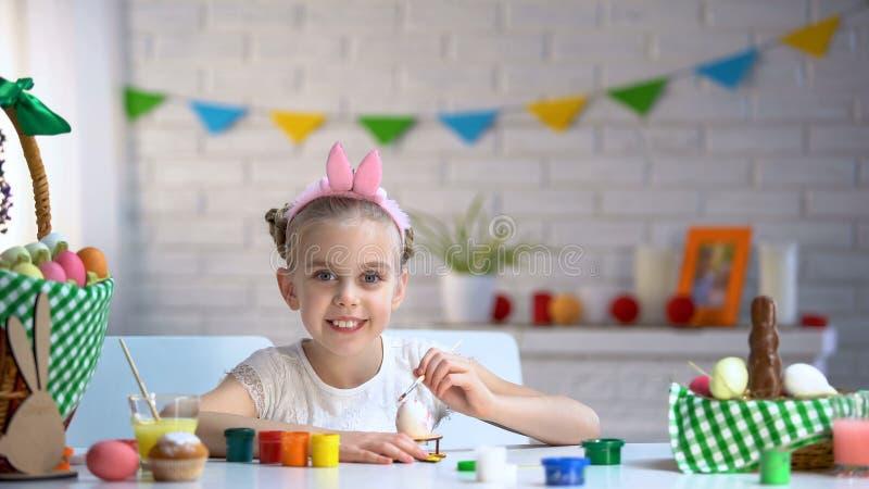 Bambina adorabile che esamina macchina fotografica, decorante le uova di Pasqua con pittura variopinta fotografia stock