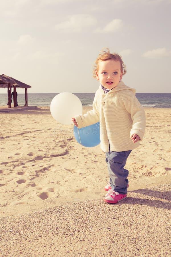 Bambina adorabile che gioca su una spiaggia fotografia stock