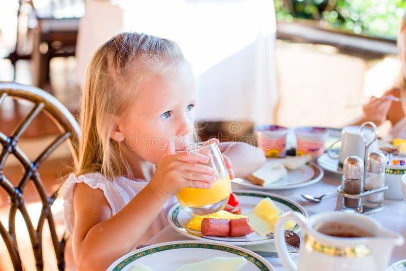 Bambina adorabile che mangia prima colazione al ristorante Il bambino sveglio gode del succo d'arancia fresco in caffè all'aperto fotografie stock