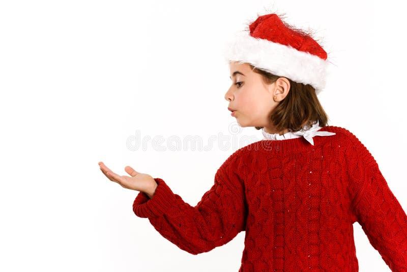 Bambina adorabile che porta il cappello di Santa che soffia alla sua mano fotografie stock libere da diritti