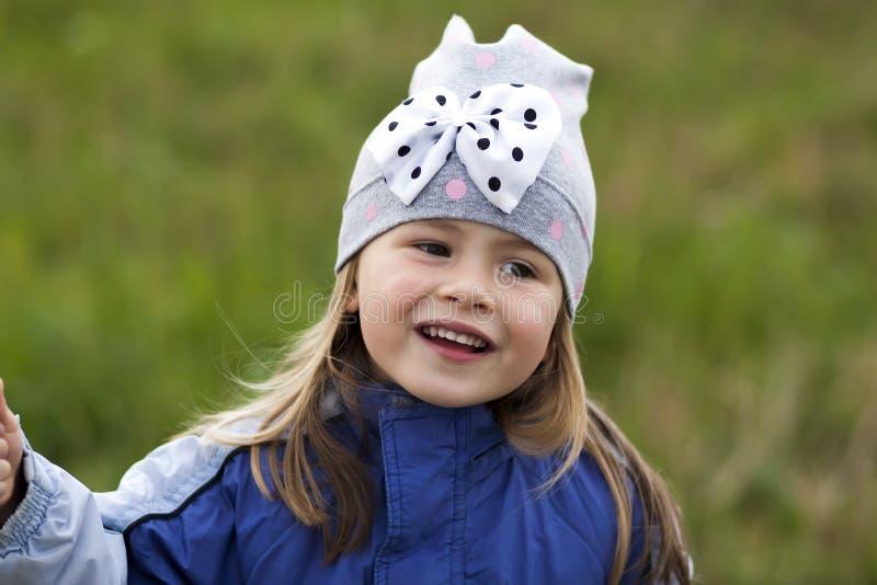 Bambina adorabile che posa sul fondo vago e che sorride dentro fotografia stock