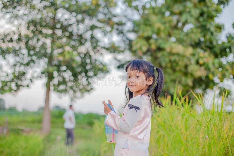 Bambina adorabile che ride in un prato - ragazza felice al tramonto immagine stock