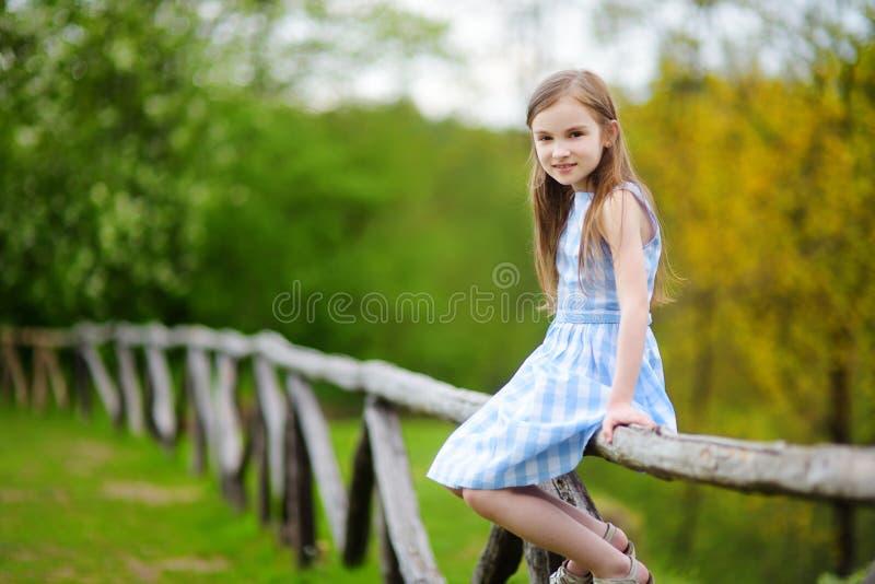 Bambina adorabile che si siede su un recinto di legno il bello giorno di molla fotografia stock
