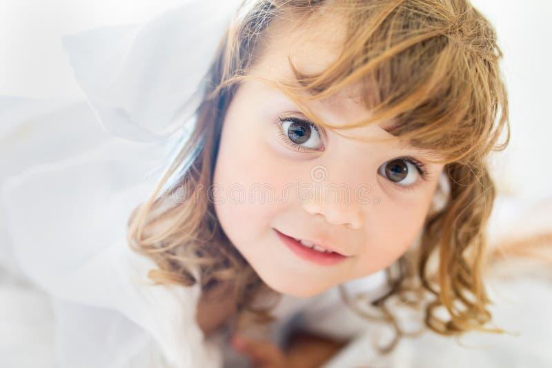 Bambina adorabile che si trova nel letto e che sorride nel primo mattino fotografia stock libera da diritti