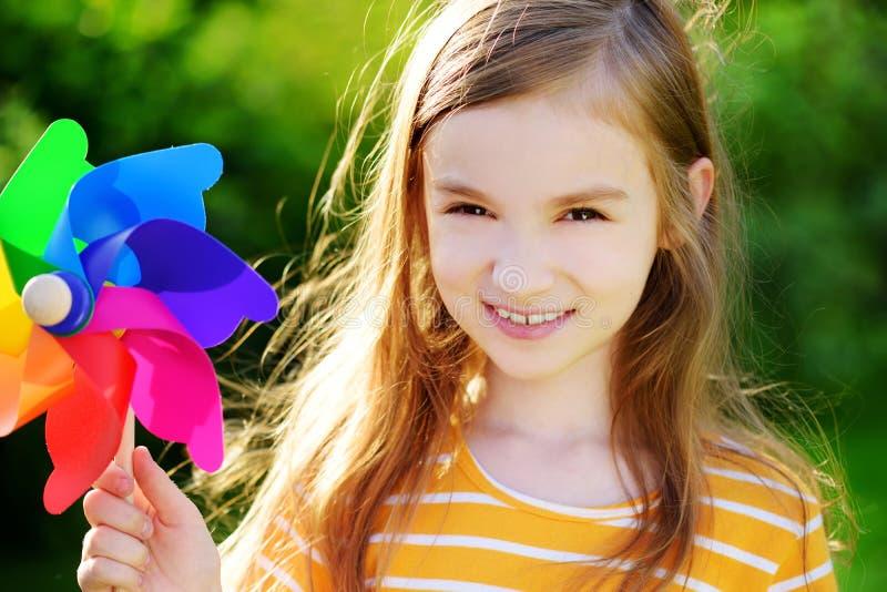 Bambina adorabile che tiene la girandola variopinta del giocattolo il giorno di estate soleggiato immagine stock libera da diritti