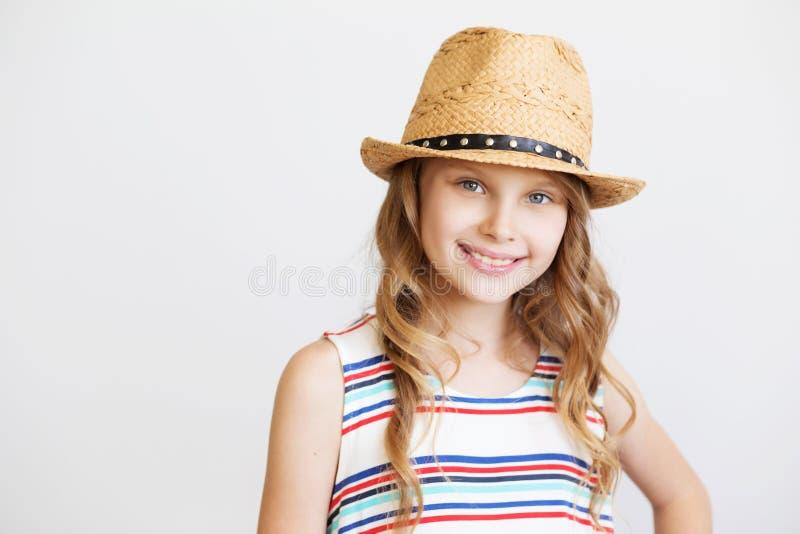 Bambina adorabile con il cappello di paglia su fondo bianco immagini stock