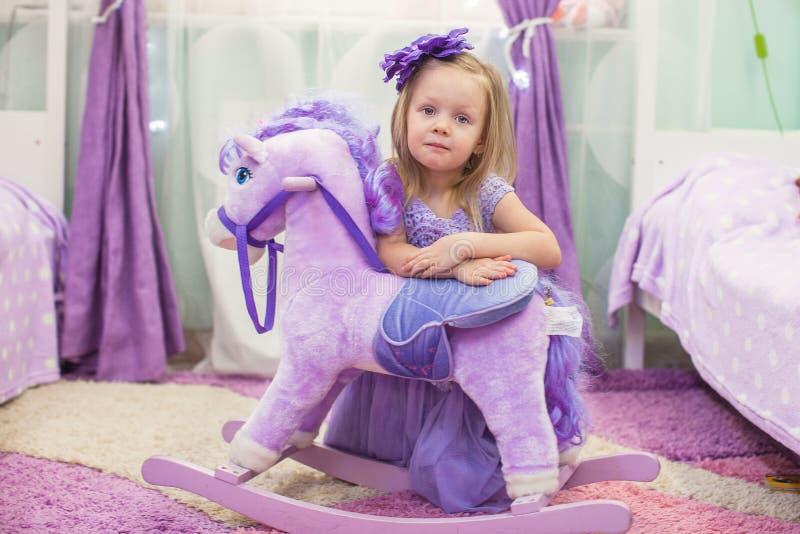 Bambina adorabile con un cavallo del giocattolo a casa immagine stock libera da diritti