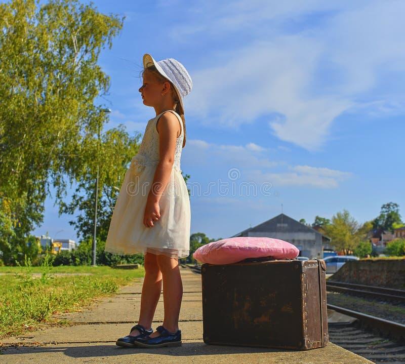 Bambina adorabile su una stazione ferroviaria, aspettante il treno con la valigia d'annata Viaggio, festa e chilhood fotografia stock