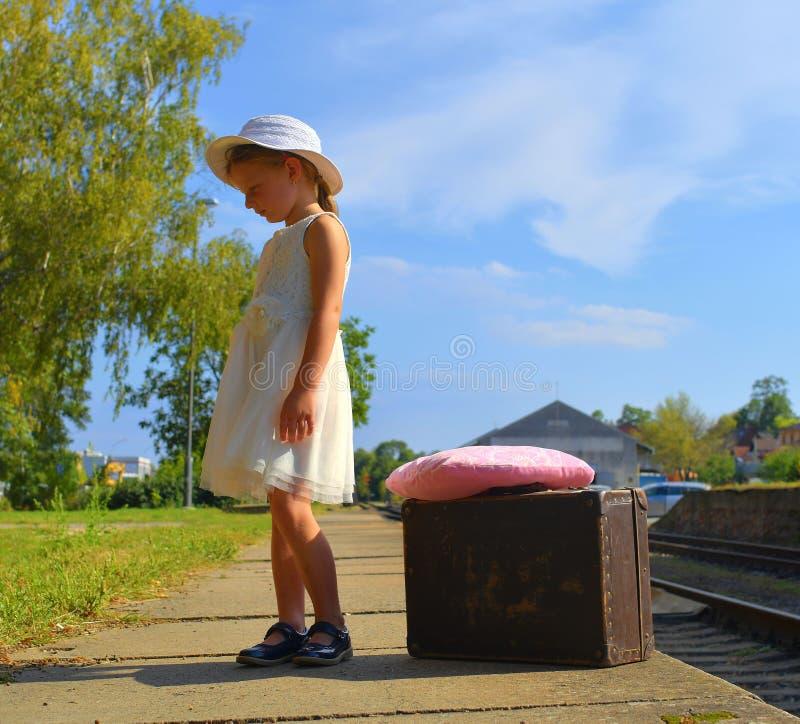Bambina adorabile su una stazione ferroviaria, aspettante il treno con la valigia d'annata Viaggio, festa e chilhood fotografia stock libera da diritti