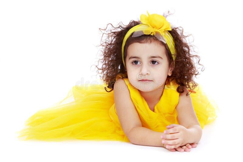 Bambina adorabile in un vestito giallo che si trova sopra fotografia stock libera da diritti