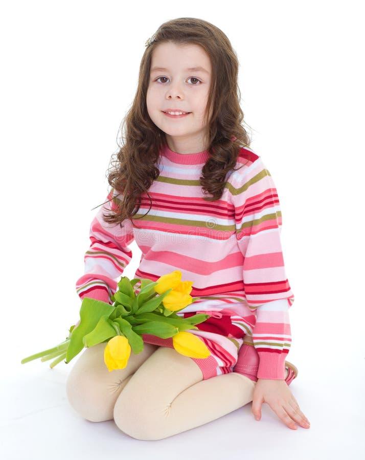 Bambina affascinante con i tulipani gialli. fotografia stock