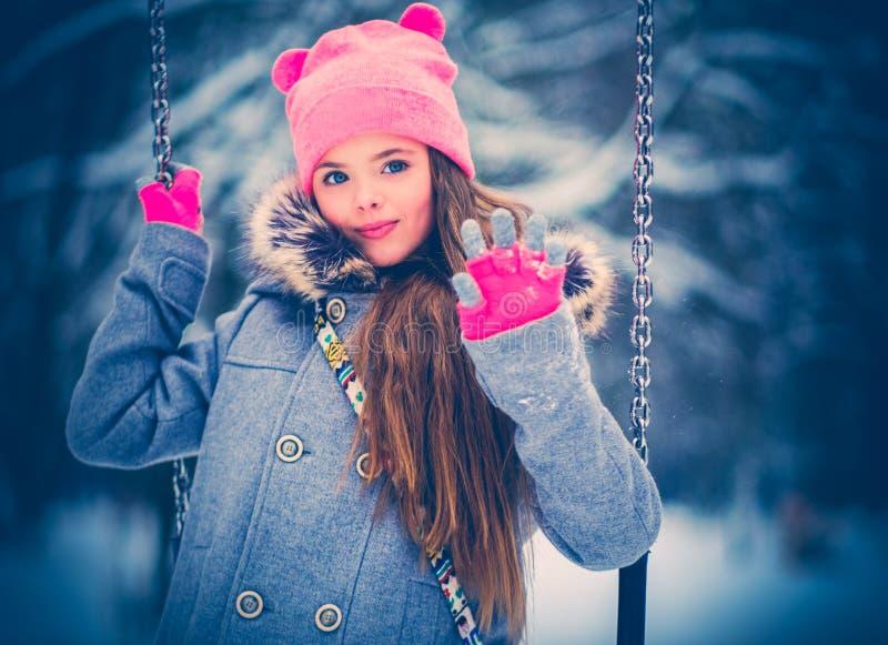 Bambina affascinante su oscillazione nell'inverno nevoso immagini stock