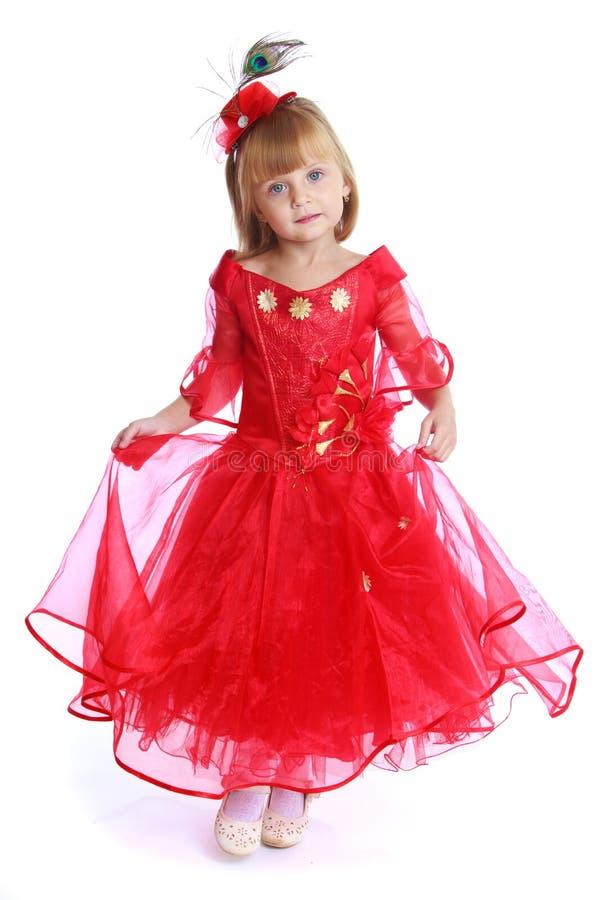 Bambina affascinante in un vestito rosso luminoso fotografie stock libere da diritti