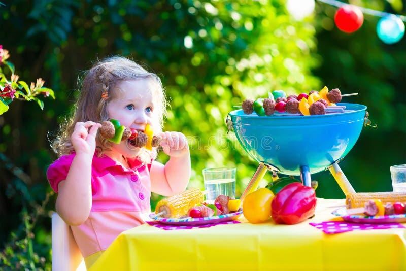 Bambina al partito della griglia del giardino immagini stock