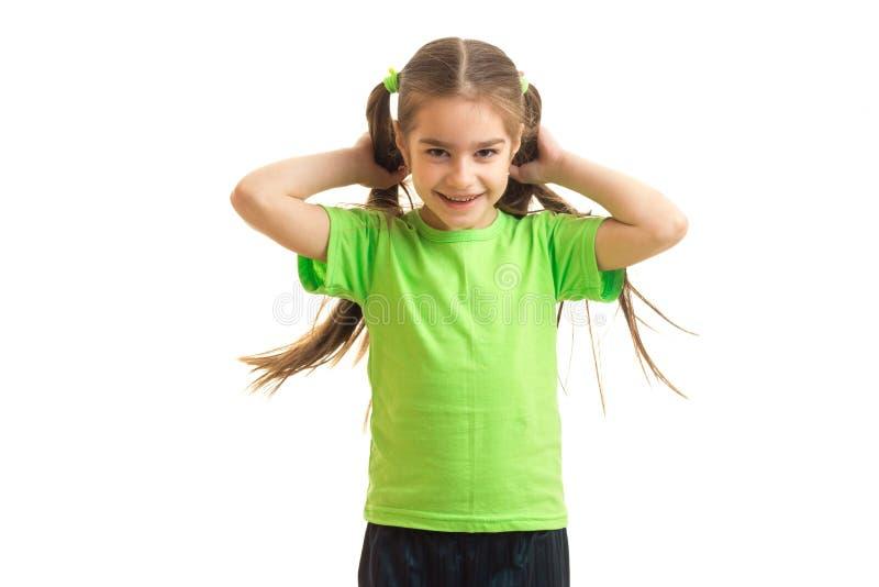 Bambina allegra in camicia verde che sorride sulla tenuta in mani un equiseto immagine stock