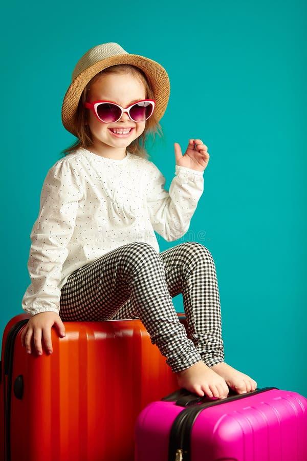 Bambina allegra in cappello di paglia ed occhiali da sole che si siedono sulle valigie, ritratto di andare in viaggio del bello b immagini stock libere da diritti