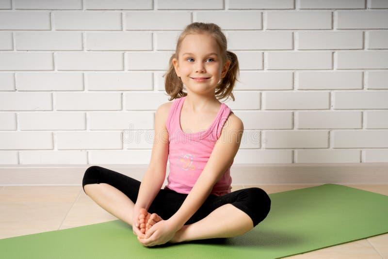 Bambina allegra che fa gli esercizi di sport sulla stuoia a casa, sugli sport dei bambini e sull'yoga fotografie stock libere da diritti