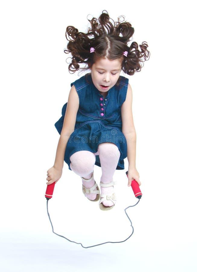 Bambina allegra che salta su un salto della corda fotografia stock libera da diritti