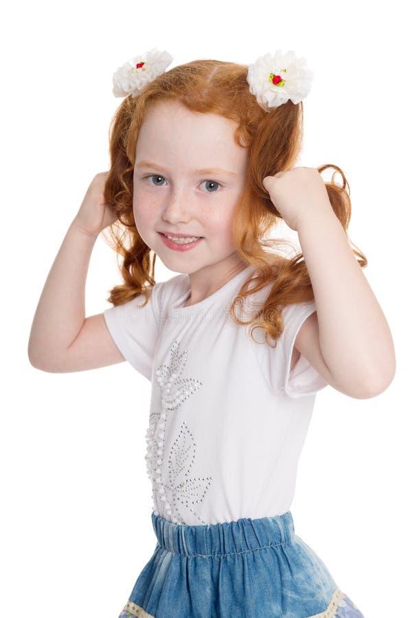 Bambina allegra che tiene i suoi capelli fotografia stock libera da diritti