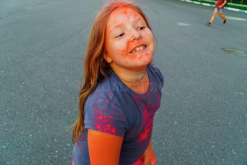 Bambina allegra con il rosa coperto capelli lunghi e la pittura asciutta porpora Holi immagini stock libere da diritti