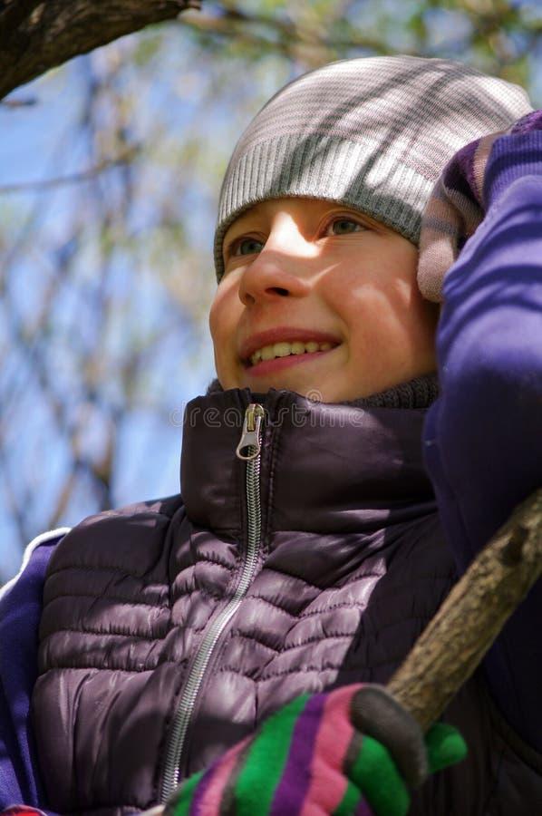 Bambina allegra divertente che scala su un albero nel parco bambini all'aperto, potrait del primo piano fotografia stock libera da diritti