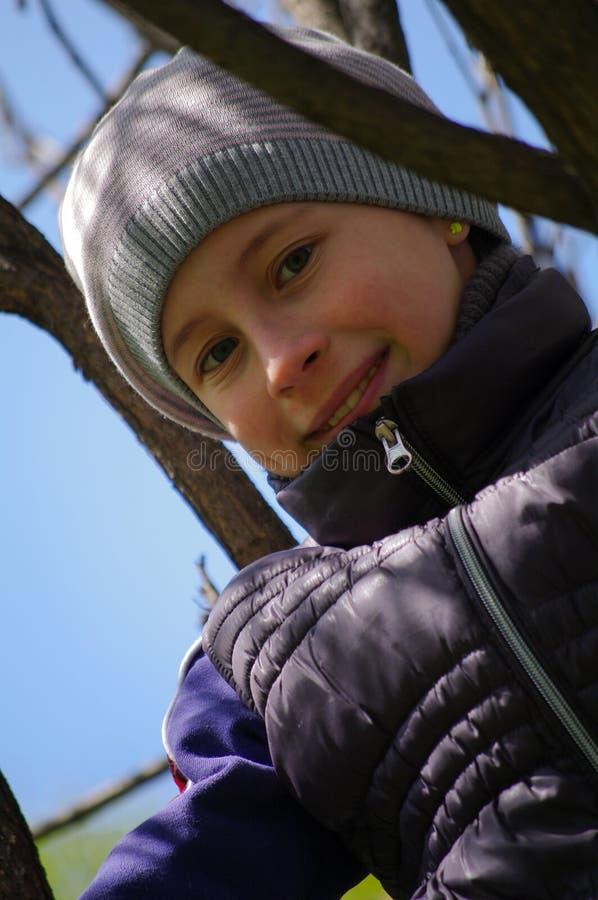Bambina allegra divertente che scala su un albero nel parco bambini all'aperto, potrait del primo piano fotografia stock