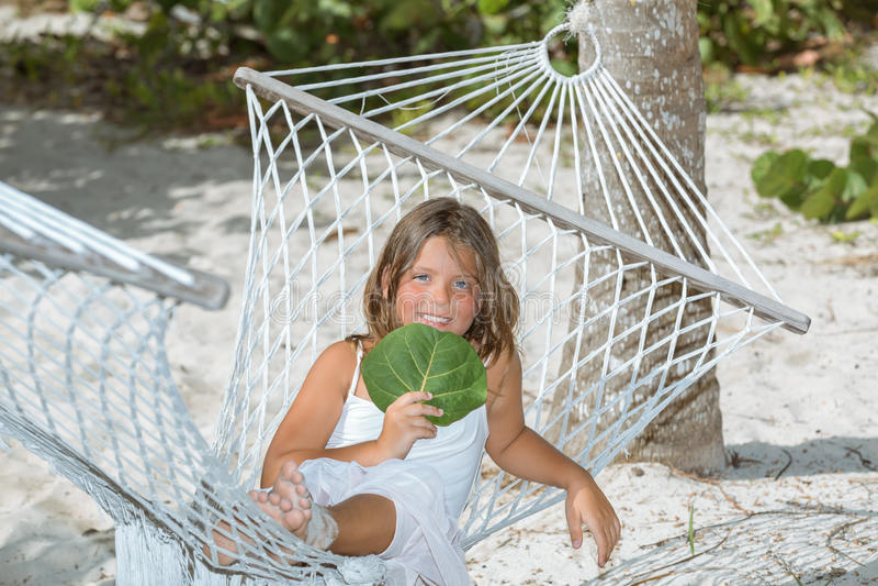 Bambina allegra felice che si siede sull'amaca in giardino tropicale fotografie stock libere da diritti